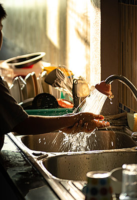 Cropped image of boy washing hands in kitchen sink at home - p1166m2105806 by Cavan Images