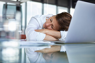 Businesswoman with closed eyes lying on glass table in office in front of laptop - p300m2012984 von Rainer Berg