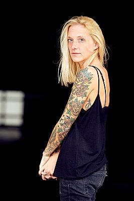 Tattooed woman with hands clasped at parking garage - p300m2268166 by Uta Konopka