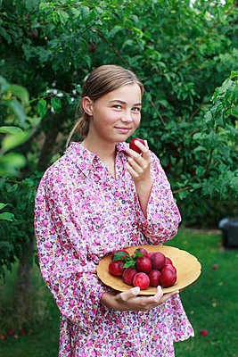 Girl holding a bowl with plums - p312m1498896 by Christina Strehlow