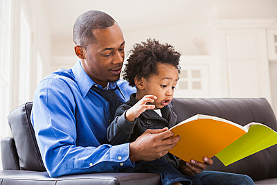 Father and son reading on sofa - p555m1464115 by Mike Kemp