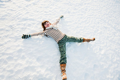 Girl making snow angel - p9243108f by Image Source