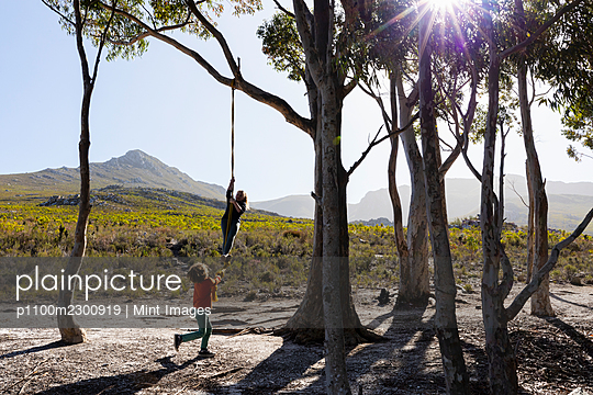 Teenage girl and younger brother using rope swing on a hiking trail - p1100m2300919 by Mint Images