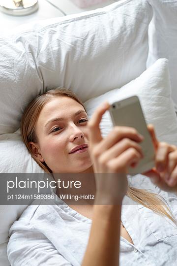 Junge Frau mit Smartphone auf dem Sofa - p1124m1589386 von Willing-Holtz