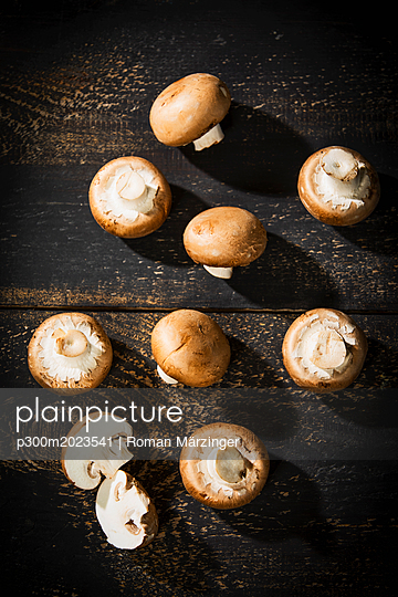 Sliced and whole Crimini Mushrooms on dark wood - p300m2023541 von Roman Märzinger