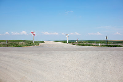 Railroad crossing along rural road and farmland,  - p1100m2002391 by Mint Images