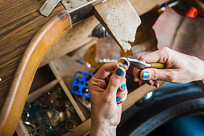 Cropped hands of female jeweller making ring with pliers in workshop - p1166m2024638 by Cavan Images