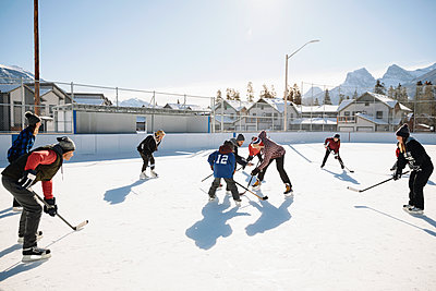 Community playing outdoor ice hockey - p1192m2087984 by Hero Images