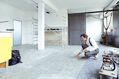 Architect checking screed at construction site - p300m1416741 by realitybites