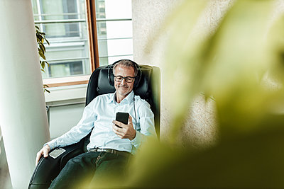 Smiling business professional on massage chair using smart phone while listening music through headphones in office corridor - p300m2266289 by Gustafsson