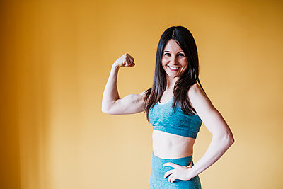 Beautiful woman flexing muscles in front of yellow wall at home - p300m2274902 by Eva Blanco