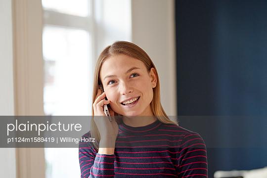 Junge Frau telefoniert mit einem Smartphone - p1124m1589419 von Willing-Holtz