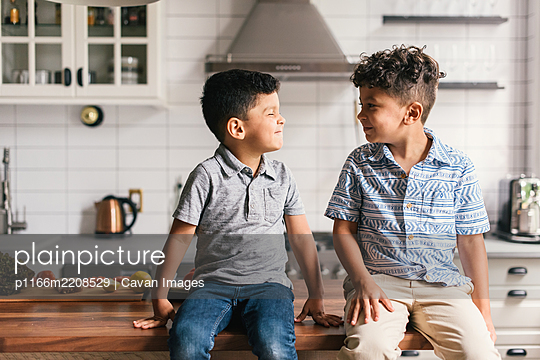 Two boys on stylish kitchen counter making funny faces at each other - p1166m2208529 by Cavan Images