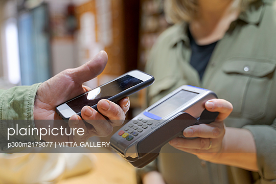 Customer paying contactless with smartphone in a shop - p300m2179877 by VITTA GALLERY