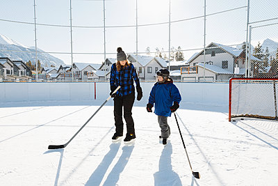 Mother and son playing outdoor ice hockey - p1192m2088047 by Hero Images