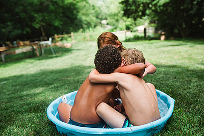 Boys in pool hugging - p1361m1477170 by Suzanne Gipson