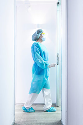 Mature female dentist walking in illuminated hallway - p300m2198389 by Jose Luis CARRASCOSA