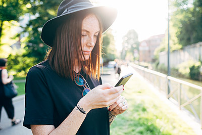 Close-up of beautiful woman wearing hat using smart phone in park - p300m2206883 by Eugenio Marongiu