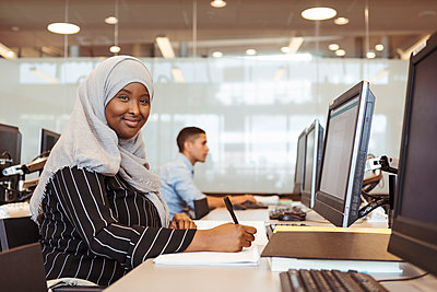 Portrait of smiling young female student writing in book while using computer at high school library - p426m2072256 by Kentaroo Tryman