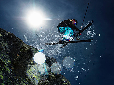Female skier jumping over rock - p4295537 by Adrian Myers
