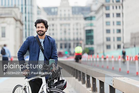 Portrait smiling businessman with bicycle and coffee on city bridge - p1023m2208400 by Paul Bradbury