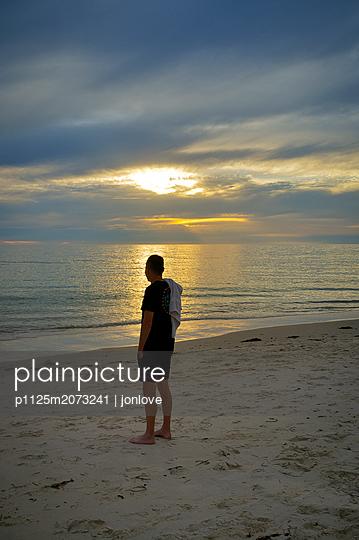 Adult man standing on beach contemplating sunset at seashore  - p1125m2073241 by jonlove