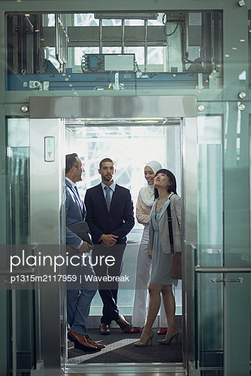 Diverse business people using lift in modern office  - p1315m2117959 by Wavebreak