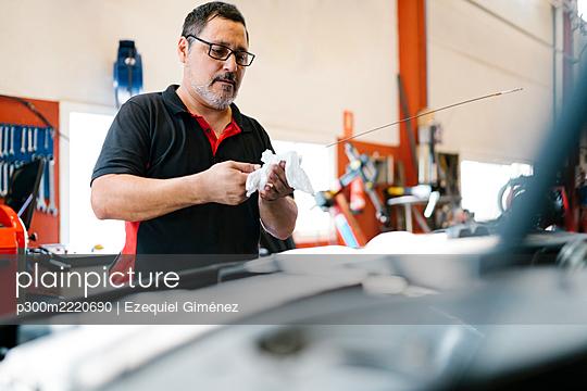 Male mechanic repairing car in auto repair shop - p300m2220690 by Ezequiel Giménez