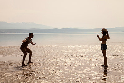 Croatia, Young woman on beach taking pictures - p1026m762666f by Dario Secen