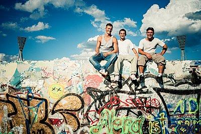 Deutschland, Berlin, Mauerpark, Jugendliche sitzen auf einer Mauer - p1093m2192937 von Sven Hagolani
