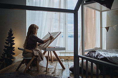 Girl drawing in her room - p1414m1590591 by Dasha Pears