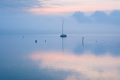 Germany, Bavaria, sailing boat on Lake Starnberg at dawn - p300m1355998 by Martin Siepmann