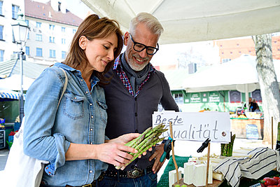 Mature couple choosing asparagus at a market stall - p300m2154736 by Eyecatcher.pro