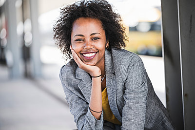 Portrait of smiling young businesswoman at the train station - p300m2160324 by Uwe Umstätter
