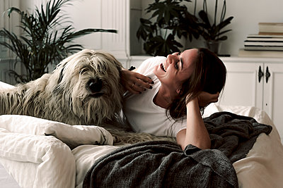 Laughing mature woman lying on bed having fun with her dog - p300m2188488 by Eloisa Ramos