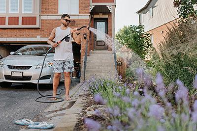 Man watering plants in garden - p300m2203107 by Sara Monika