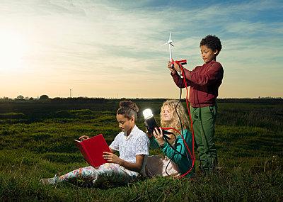 Children using miniature wind turbine to power light bulb, Breda, Netherlands - p429m1206928 by Mischa Keijser