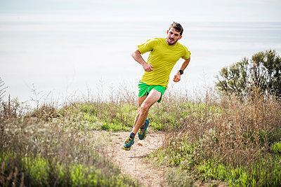Runner jogging on cliff top, Santa Barbara, California, USA - p429m2075318 by JFCreatives