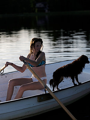 Young woman and dog in rowing boat - p551m2134195 by Kai Peters