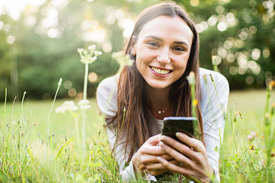 Portrait of young woman using smart phone while lying in park - p623m2294820 by Gabriel Sanchez