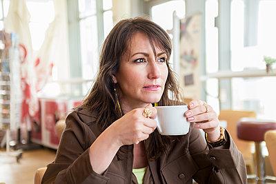 Junge Frau trinkt eine Tasse Kaffee - p890m1467371 von Mielek
