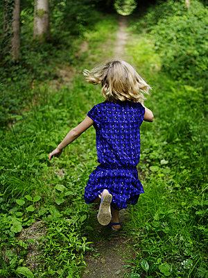 Kleines Mädchen läuft im Wald - p945m1467745 von aurelia frey