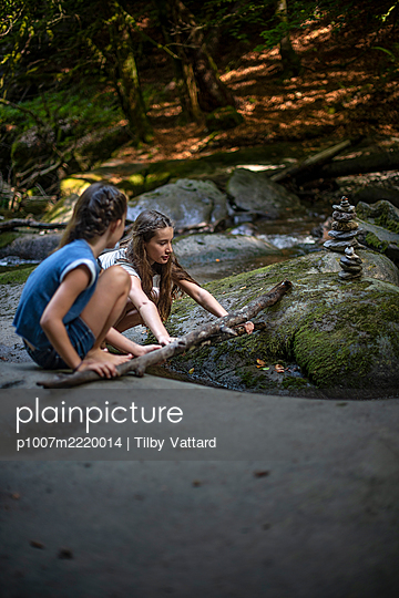 Two girls playing on the riverbank with a branch - p1007m2220014 by Tilby Vattard