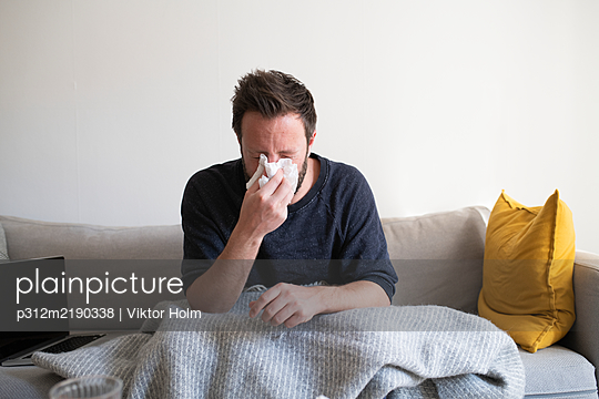 Man on sofa blowing his nose - p312m2190338 by Viktor Holm