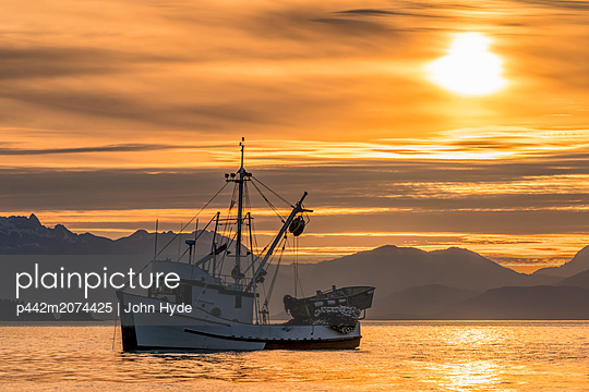 Seiner anchored in Amalga Harbor at sunset awaiting a commercial salmon opening, Southeast Alaska; Juneau, Alaska, United States of America - p442m2074425 by John Hyde