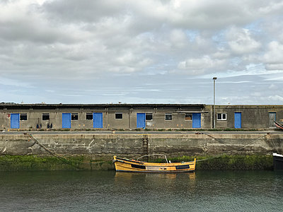 Small yellow boat moored by blue doors - p1048m2016493 by Mark Wagner