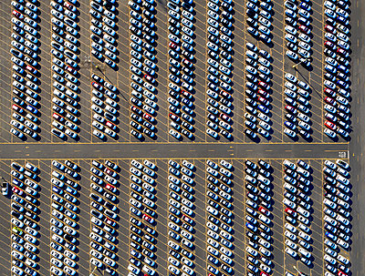 Aerial view of a car distribution centre, new cars parked in rows on a lot ready for sale.   - p1100m1216254 by Mint Images