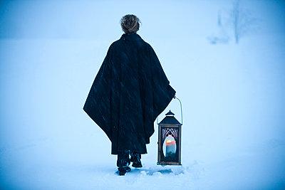 Frau mit einer Laterne geht durch Schnee, Steiermark, Österreich - p1316m1160652 von Harald Eisenberger