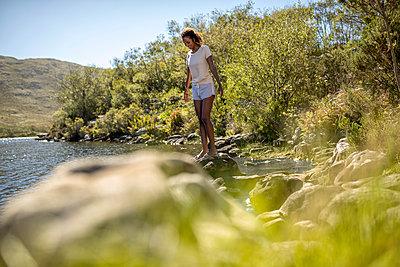 Junge Frau an einem Flussufer - p1355m1574221 von Tomasrodriguez