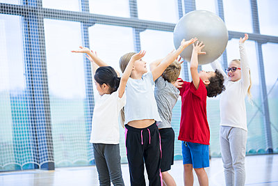 Pupils handing over gym ball in gym class - p300m2005304 von Fotoagentur WESTEND61